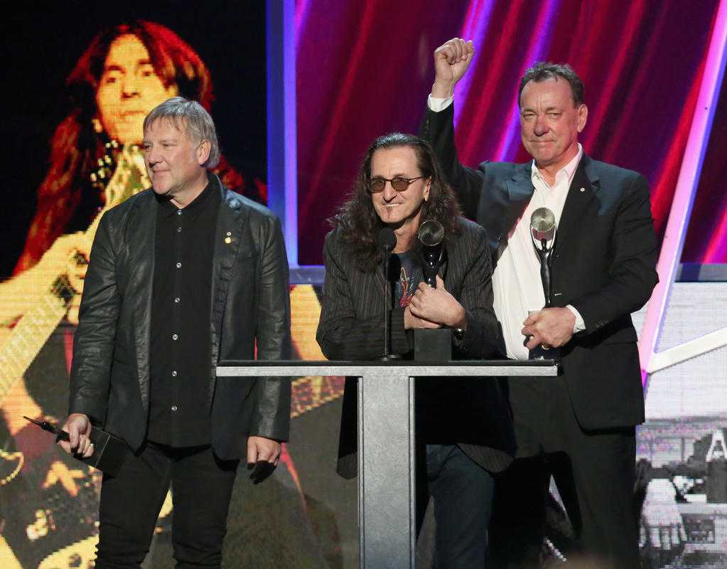 Musicians Alex Lifeson, Geddy Lee, and Neal Peart of the progressive rock band Rush being inducted into the Rock and Roll Hall of Fame in Cleveland, Ohio in 2013